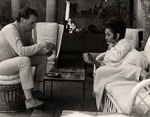 Actors Richard Burton and Elizabeth Taylor (wearing caftan from Givenchy boutique), seated and lounging and playing gin while on vacation at La Fiorentina, Saint-Jean-Cap-Ferrat, 1967