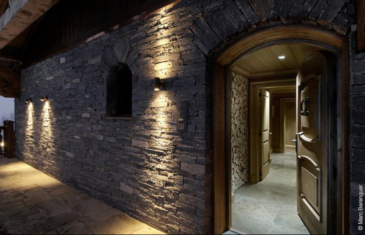 Entrance with stone wall and front door in Courchevel